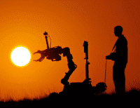 man testing a robotic arm in the sun